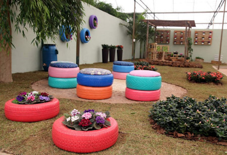 just paint a tire with shiny bright colors and make cool designs over it take care while hanging you can use both the ropes and chains to hang it - Garden Ideas Using Tyres