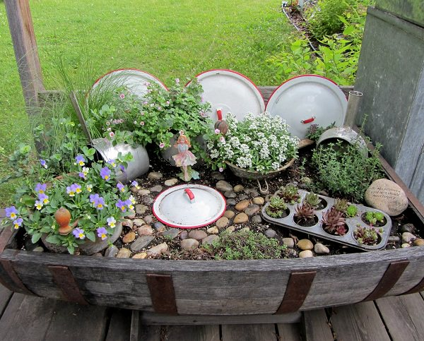 fairy gardens are in trend if you a have a barrel or a big planter and some unused kitchen utensils like ricers pots a scoop pot lids and a muffin tin